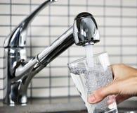 заполняя стеклянная вода из крана Стоковая Фотография