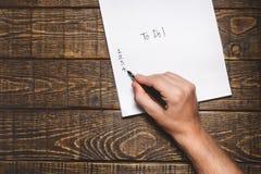 Заполнения персоны для того чтобы сделать список вещей в тетради, взгляд сверху Концепция идей процесса стратегии планирования па стоковые изображения