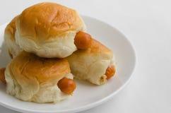 Заполненные плюшки сосиски в белой плите Стоковые Фото