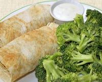 2 заполнили обручи Tortilla с стороной свежего сырцового брокколи и контейнера сметанообразной шлихты Стоковые Фото
