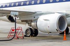 Заправлять топливом воздушные судн, взгляд крыла, шланг, двигатель Обслуживание авиапорта Стоковое фото RF