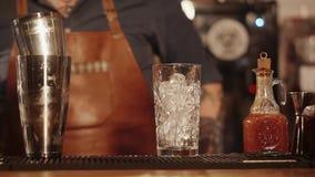 Заприте шкаф с высокорослым стеклом с кубами льда внутрь, бармен двигает в предпосылку сток-видео