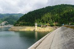 Запруда Pecingeanu на реке Dambovita озеро накопления, башня входа и зеленая предпосылка леса Стоковые Фотографии RF