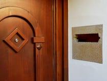 Запятнанная коричневая деревянная входная дверь с peephole и каменным слотом почты стоковое изображение rf