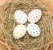 4 запятнанных покрашенных пасхального яйца в сене Стоковые Фото