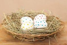 4 запятнанных покрашенных пасхального яйца в сене Стоковые Изображения RF