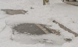 2 заплаты черного асфальта окруженной снегом Стоковые Фото