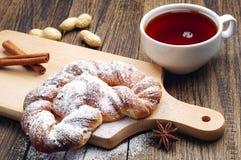 Заплетенный крупный план плюшки и чашки чаю Стоковое Изображение RF