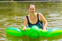 Заплывание девушки в реке с раздувной черепахой Стоковое Фото