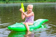 Заплывание девушки в реке с раздувным крокодилом Стоковая Фотография RF