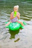 Заплывание девушки в реке с раздувным крокодилом Стоковое Фото