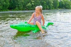 Заплывание девушки в реке с раздувным крокодилом Стоковое Изображение