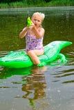 Заплывание девушки в реке с раздувным крокодилом Стоковые Изображения