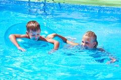 Заплывание девушки и мальчика в бассейн курорта Стоковое фото RF