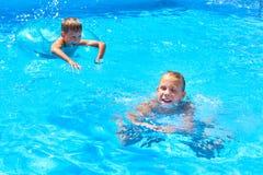 Заплывание девушки и мальчика в бассейн курорта Стоковые Изображения RF