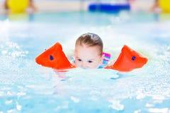 Заплывание девушки малыша в бассейне с стороной подводной Стоковая Фотография