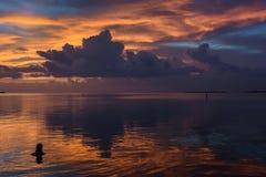 Заплывание женщины во время захода солнца на тропическом положении портового района Стоковое Изображение