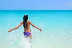 Заплывание женщины потехи каникул пляжа брызгая воду Стоковое фото RF