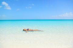 Заплывание женщины пляжа в океане ослабляя стоковое изображение