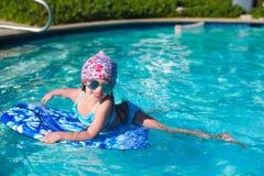 Заплывание маленькой девочки на surfboard внутри Стоковые Изображения RF