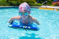 Заплывание маленькой девочки на surfboard внутри Стоковое Изображение