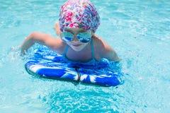 Заплывание маленькой девочки на surfboard внутри Стоковые Фото