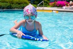 Заплывание маленькой девочки на surfboard внутри Стоковые Фотографии RF