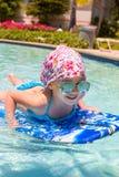 Заплывание маленькой девочки на surfboard внутри Стоковое Изображение RF