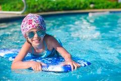 Заплывание маленькой девочки на surfboard внутри Стоковая Фотография