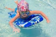 Заплывание маленькой девочки на surfboard внутри Стоковые Изображения