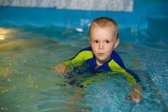 Заплывание мальчика в бассейне Стоковые Фото