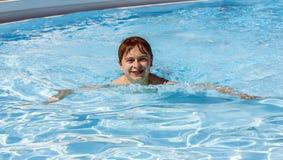 Заплывание мальчика в бассейне Стоковая Фотография RF