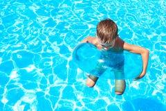 Заплывание мальчика в бассейн Стоковые Фото