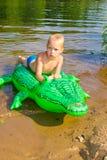 Заплывание мальчика в реке с раздувным crocodil Стоковая Фотография RF