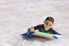 Заплывание мальчика на доске буг Стоковые Фото
