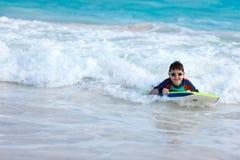 Заплывание мальчика на доске буг Стоковые Фотографии RF