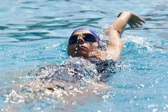 Заплывание молодой женщины в бассейне стоковая фотография