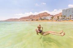 Заплывание молодой женщины туристское плавая солёная вода, мертвое море Стоковое Фото