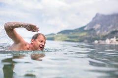 Заплывание старшего человека в море/океане Стоковое Изображение