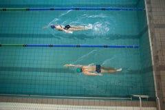 Заплывание человека и женщины в бассейне Стоковые Фотографии RF