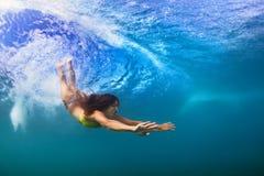 Заплыв подводный, пикирование молодой женщины под океанской волной Стоковое фото RF