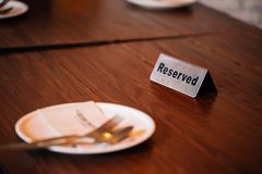 ` Зарезервировало знак ` на обеденном столе в ресторане с ложкой, вилкой и плитой стоковое фото rf