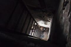 Заржаветая лестница металла идя вниз от темной комнаты стоковая фотография rf