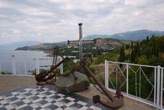 Заржаветые анкеры при цепи лежа на камне на платформе Обозревать прибрежную линию моря и дома на Стоковое Изображение RF