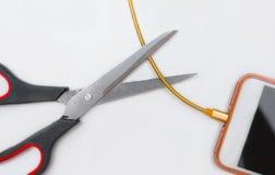 Зарядный кабель smartphone вырезывания при ножницы изолированные на белизне Стоковые Фото