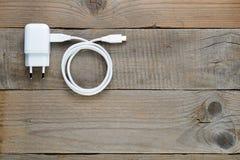 Заряжатель Smartphone или таблетки на таблице Стоковая Фотография