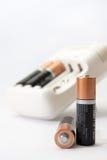 Заряжатель и батареи батареи на белой предпосылке Стоковое Изображение RF