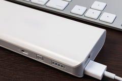 Заряжатель кабеля USB с банком энергии на деревянном столе Стоковая Фотография RF