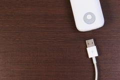 Заряжатель кабеля USB с банком энергии на деревянном столе Стоковые Фотографии RF
