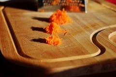 Заскрежетанная морковь лежа на деревянной доске Стоковое Изображение
